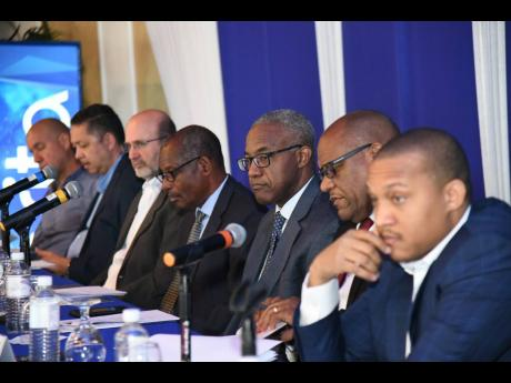 Directors of Barita Investments Limited seated at the head table, from left, James Godfrey, Phillip Lee, Duncan Stewart, Carl Domville, Robert Drummond, Managing Director/Company Secretary Ian McNaughton and Deputy Chairman Paul Simpson, at the company's annual general meeting at Terra Nova All-Suites Hotel in St Andrew on Thursday, March 21.