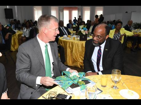 Earl Jarrett, CEO, The Jamaica National Group, makes a point to retired US Army General Stanley McChrystal following his presentation to private-sector leaders during a breakfast function recently.