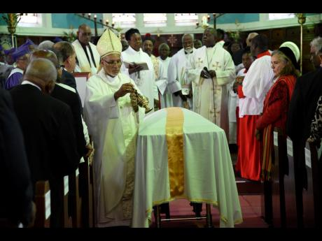 Howard Gregory, Bishop of Jamaica and the Cayman Islands, performs the final rites at the funeral of Dosel Owen 'Hurry Hurry' Sinclair at the St George's Anglican Church in Savanna-la-Mar, Westmoreland, on Saturday.