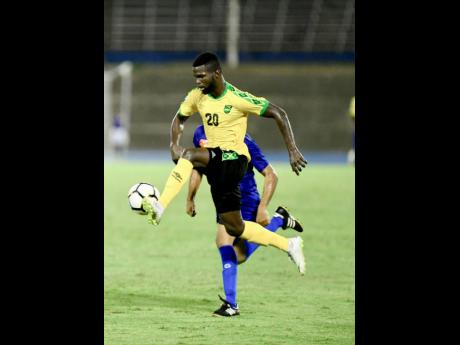 Jamaica's Kemar Lawrence (foreground) takes the ball under control while being chased by Cayman Islands defender Kyle Santamaria during their CONCACAF Nations League game at the National Stadium on Sunday, September 9, 2018.