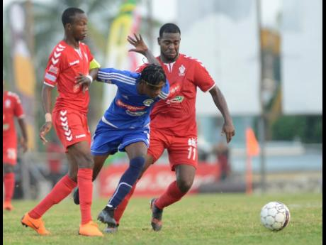 Mount Pleasant FA's Daniel Green (centre) drives forward, riding the challenge of UWI FC defenders Rochane Smith (left) and Dwayne Smith during the first leg of their Red Stripe Premier League quarter-final match-up at the Anthony Spaulding Sports Complex yesterday.