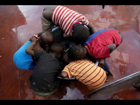 Kids scrape for remaining rice inside a pot at a displacement centre in Beira, Mozambique, on Friday, March 22.