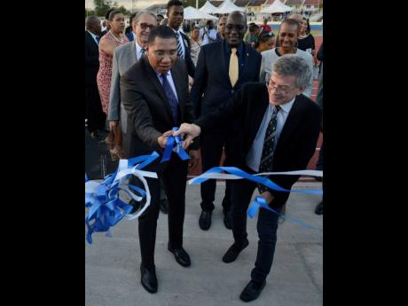 Prime Minister Andrew Holness (left) and Michael Ashenheim, benefactor, cut the ribbon for the official opening of the Ashenheim Stadium at Jamaica College on February 20. Looking on are R. Danny Williams (behind Holness), then Education Minister Ruel Reid (centre), and Energy Minister Fayval Williams.