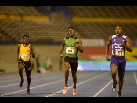 Calabar's Christopher Taylor (centre) crosses the line in the Class One boys 200m heats ahead of  Kingston College's Oshane Peart at the ISSA/GraceKennedy Boys and Girls' Athletics Championships at the National Stadium last night. Taylor clocked 21.69 seconds for the win.