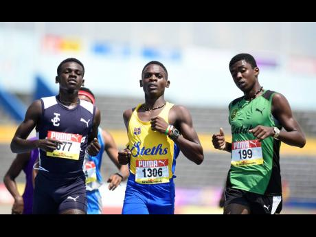 Fabian Campbell (left) of Jamaica College wins heat one of the class one boys 1500m event ahead of Kevroy Venson of Calabar (right) and Davian Gary of St Elizabeth Technical High at the ISSA/GraceKennedy Boys and Girls' Athletics Championships at the National Stadium in Kingston on Wednesday March 27, 2019.
