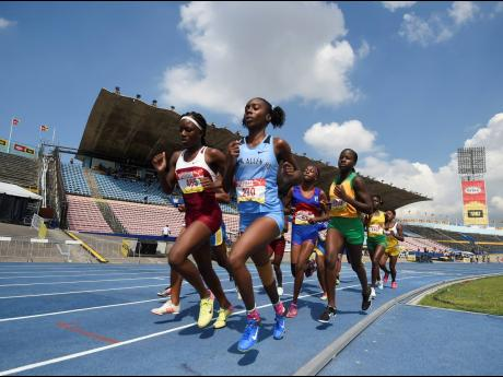 Samantha Pryce, 4:52.09, (foreground left) of Holmwood Technical on her way to winning Heat Two of the Class Two girls 1500m event at the ISSA/GraceKennedy Boys and Girls Athletics Championships at the The National Stadium yesterday.