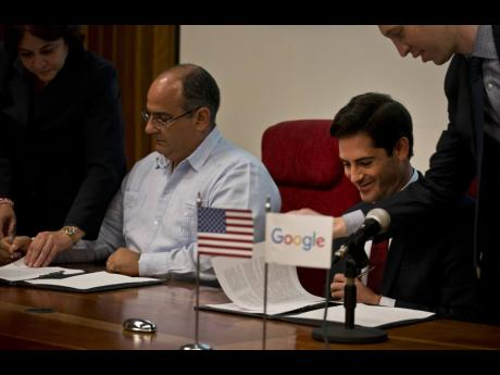 Google's head of Cuba operations, Brett Perlmutter, right, signs a deal with Luis Adolfo Iglesias Reyes, vice president of investments of Etecsa, left, in Havana, Cuba, yesterday.