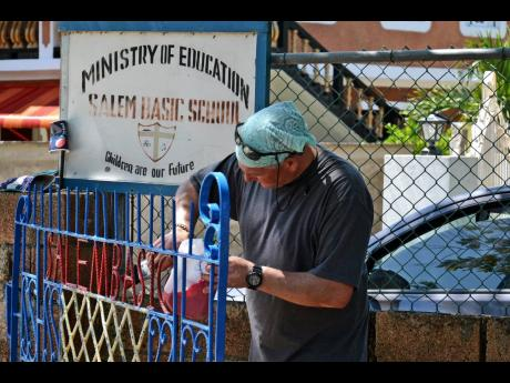 A volunteer from Sober Vacations International paints a gate at Salem Basic School.