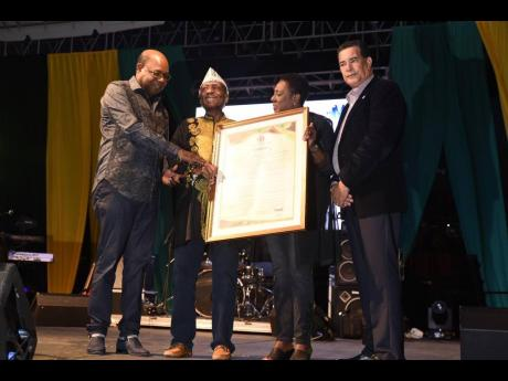 James 'Jimmy Cliff' Chambers (second left) being presented with a citation in his honour by Tourism Minister Ed Bartlett (left); Montego Bay's mayor, Homer Davis, and Minister of Culture Olivia 'Babsy' Grange at the unveiling of Jimmy Cliff Boulevard, held at the Old Hospital Park in Montego Bay to honour the reggae icon.