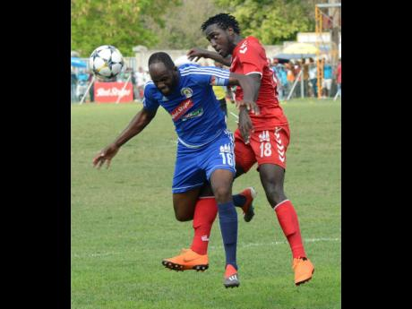 Mount Pleasant FA's Francois Swaby (left) and UWI FC's Michael Heaven (right) tussle for ball possession during the second-leg quarter-final tie of the Red Stripe Premier League at Drax Hall, St Ann, yesterday.