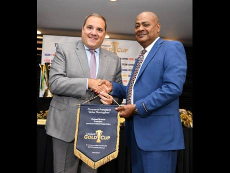Ricardo Makyn/Chief Photo Editor  Victor Montagliani (left) Concacaf president, makes a presentation to Jamaica Football Federation (JFF) president Michael Ricketts during a press conference yesterday at the Jamaica Pegasus, to announce that the island will host two matches this year's Concacaf Gold Cup.