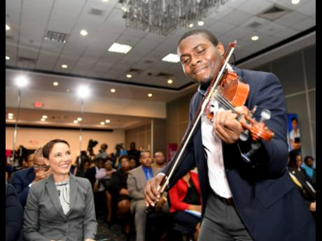 Foreign Affairs Minister Kamina Johnson Smith looks on while Michael Wilson plays the violin at the launch of the eighth Biennial Jamaica Diaspora Conference at The Jamaica Pegasus hotel yesterday. The conference will be held from June 16-20 at the Jamaica Conference Centre.