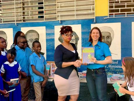 Robin Heffernan (right), project coordinator at the Violence Prevention Alliance presents  Shelley-Ann Bennett, librarian at the Windward Road Primary and Junior High School with books donated by the students of the American International School of Kingston (AISK). Some 200 books were donated to the school as part of Peace Month activities organised by the VPA in collaboration with AISK.
