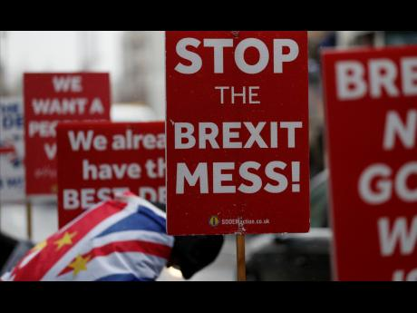 Anti-Brexit protesters with placards stand in the rain during demonstrations outside the Houses of Parliament in London on Tuesday, April 2.