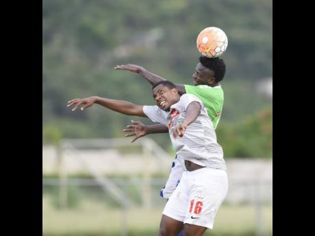Ladale Richie of Mount Pleasant Football Academy heads the ball over Andrae Bernal of UWI FC (front) during a Red Stripe Premier League match at University of the West Indies last season.