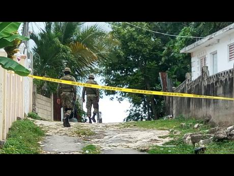 Soldiers make their way to an area where five persons were shot, two fatally, in Rose Heights, St James, last month.