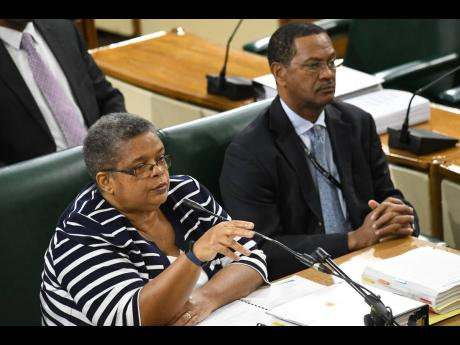 Carol Palmer, permanent secretary in the Ministry of Energy, Science and Technology, and Winston Watson, acting general manager of Petrojam, answering questions at the Public Accounts Committee meeting at Gordon House yesterday.