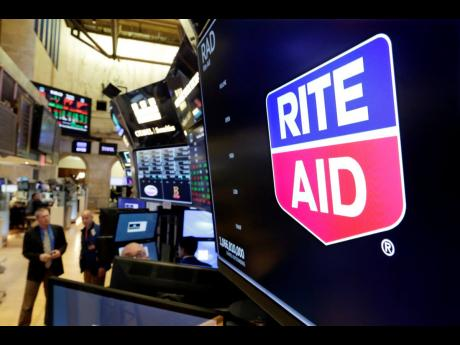 The logo for Rite Aid is displayed above a trading post on the floor of the New York Stock Exchange.