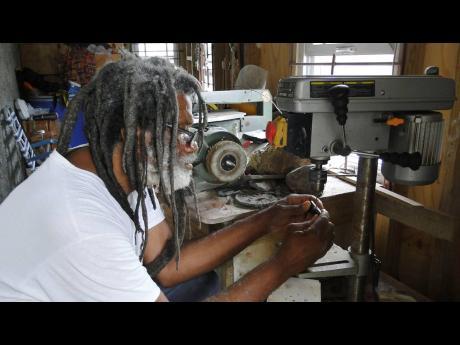 Ras Mel piercing a pendant in his workshop.