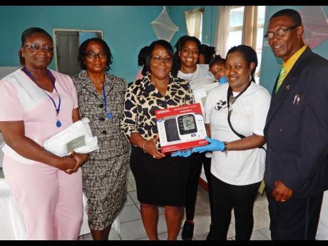 Thora Daley (second right) hands over a blood pressure monitor to Yvett Duncan, inspector of the Poor, during a  handover ceremony at the St Ann Infirmary. Others in pictured (from left) are Rosebelle Clarke, Ity Vickers, and Councillor Dallas Dickenson, chairman of the Poor Relief Department in the St Ann Municipal Corporation.