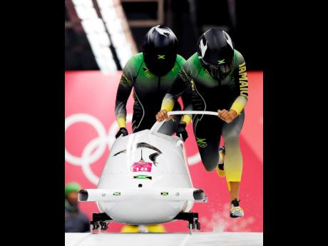 Jamaican bobsledder Carrie Russell (left) and teammate Jazmine Fenlator-Victorian get their heat started during a Women's Two Man Bobsled event at the 2018 Winter Olympic Games in PyeongChang, South Korea. Russell is now attempting to qualify for the Monobob event at the 2022 Winter Olympics in Beijing, China.
