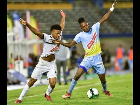 Alex Marshall (left) of Cavalier FC and Waterhouse's Ricardo Thomas in a tussle for possession of the ball in the Red Stripe Premier League second leg semi final played at the National Stadium in Kingston earlier this evening.