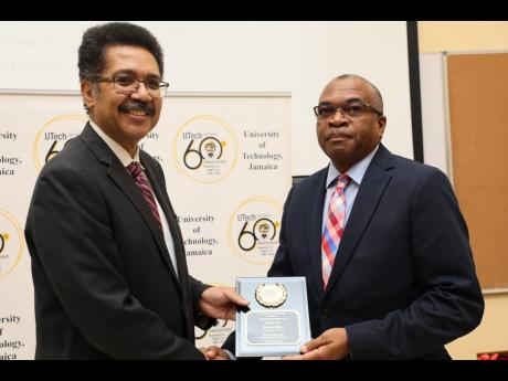Professor Stephen Vasciannie, president, UTech, Jamaica, presents the Outstanding Alumni Award for Service to Country to Trevor Riley, group CEO  of the Shipping Association of Jamaica.