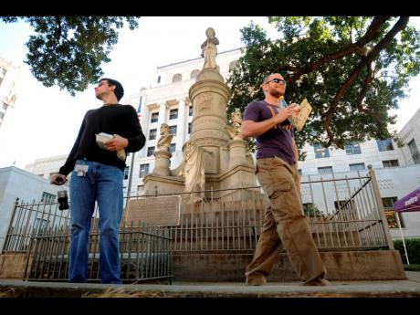 In this November 4, 2011 file photo, Sean Bordelon (left) and Raphiel Heard, of Shreveport, pause after reading the inscription on the Confederate soldier's monument in front of the Caddo Parish Courthouse in Shreveport, Louisiana. A federal appeals court says a judge was right when he cleared the way to remove a Confederate monument at a north Louisiana courthouse.