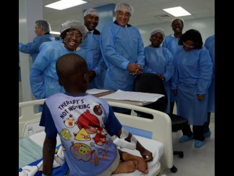 From left: Dr Venice Guntley McKenzie (left); Member of Parliament Julian Robinson; Health Minister Dr Christopher Tufton; and Digicel Foundation CEO Karlene Dawson speak with a young patient at the newly opened cardiac centre at the Bustamante Hospital for Children yesterday.