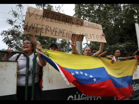 """People hold a Venezuelan flag and the Spanish message: """"Venezuelans demand military intervention,"""" on the sidelines of a visit by US Secretary of State Mike Pompeo in La Parada near Cucuta, Colombia, on the border with Venezuela, Sunday, April 14. (AP)"""