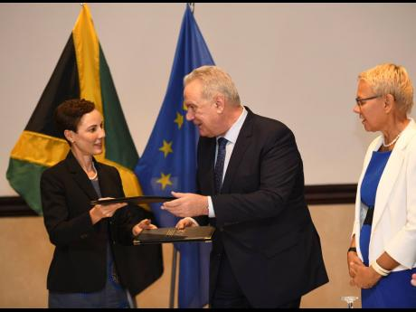 From left: Foreign Affairs Minister Kamina Johnson Smith exchanges documents with Nevin Mimica, European commissioner for international cooperation and development, and Malgorzata Wasilewska, head of the European Union Delegation to Jamaica, after a signing ceremony for improved forest management and support for public financial management reform between the Government of Jamaica and the European Union at The Jamaica Pegasus hotel yesterday.