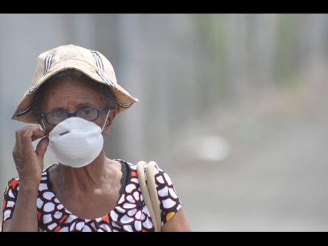 A senior citizen covers her nose with a dust mask in Duhaney Park due to smoke caused by a fire at the Riverton City dump on Saturday, March 14, 2015.