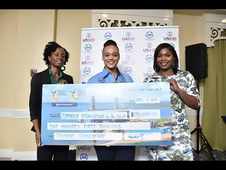 Jamaica Energy Partners (JEP) Customer Service Representative, Patrice Howell (right), presents JEP's contributionto Jamaica Association for the Deaf executives - Kimberley Sherlock, executive director (centre), and Deniese Badroe, director of Business Development with a symbolic cheque valued at $150,000.00 in scholarships for students enrolled at the Jamaica Association for the Deaf. The scholarships will go towards covering tuition, books, boarding and meals for students.