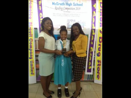 First-place winner Hytasha Barnes (centre) is flanked by competition organiser Andrea Bailey (right) and assistant librarian Rushenna McFachron.