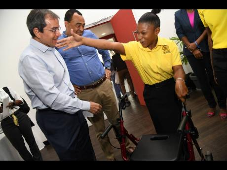 Tiffany Thomas, Food For the Poor ambassador, greets (from left) Andrew Mahfood, chairman of Food For the Poor, and Dr Christopher Tufton, minister of health, during the charity's launch of its fifth annual  5K Run/Walk at  the Spanish Court Hotel, St Andrew on Tuesday.