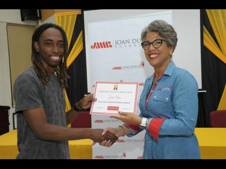 A delighted Jordan Payne (left) receives his certificate of participation from JMMB Joan Duncan Foundation CEO Kim Mair, in recognition of his involvement in the two-day social media marketing training workshop, which was held recently at the UWI, Mona library.