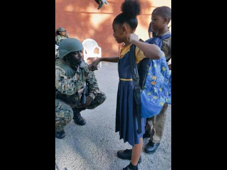 A member of the joint security forces interacts with children in Mount Salem, St James, in this 2017 file photo.