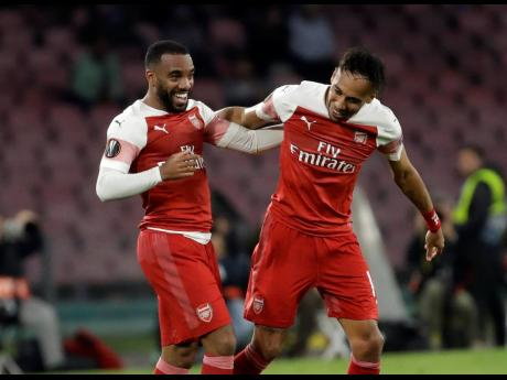 Arsenal's Alexandre Lacazette (left) celebrates after scoring his side's first goal during the Europa League second leg quarter-final match between Napoli and Arsenal at San Paolo stadium in Naples, Italy, yesterday.