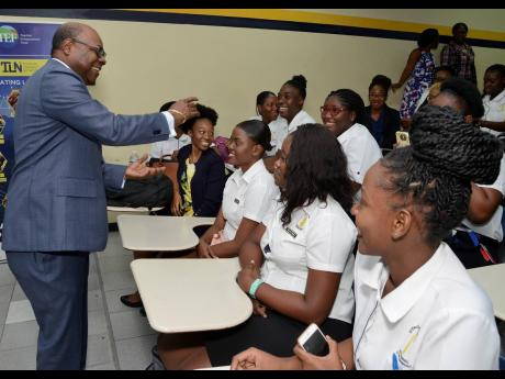 Tourism Minister Edmund Bartlett congratulates graduates at the Jamaica Blue Mountain Coffee Festival Volunteer Programme during the awards ceremony at the University of Technology, Jamaica, on Tuesday.