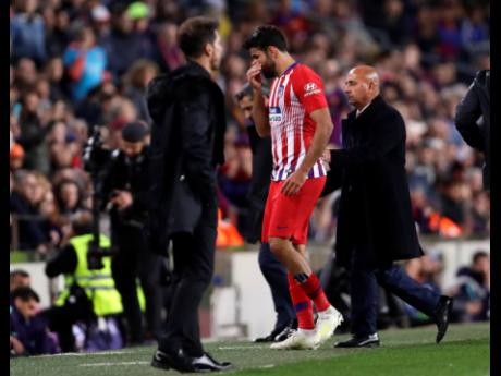 Atletico forward Diego Costa walks off the pitch after receiving a red card for insulting referee Jesus Gil Manzano during a Spanish La Liga match between FC Barcelona and Atletico Madrid at the Camp Nou stadium in Barcelona, Spain, Saturday, April 6.