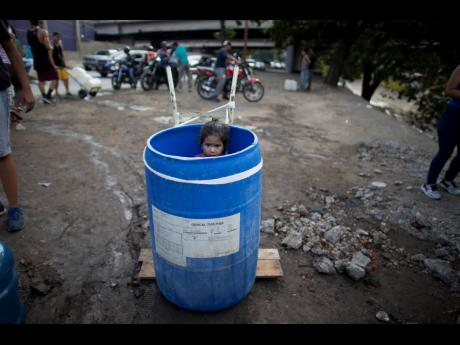 In this March 11, 2019, file photo, a little girl stands inside a plastic barrel while her family waits to collect water from an open pipe above the Guaire River, during rolling blackouts in Caracas, Venezuela.