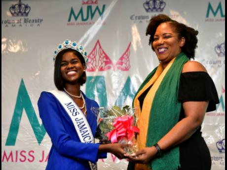 Miss Jamaica World franchise holder Dahlia Harris is presented with a bouquet by Miss Jamaica World 2018 Kadijah Robinson at the launch of Miss Jamaica World 2019 at The Jamaica Pegasus hotel in New Kingston last Thursday.