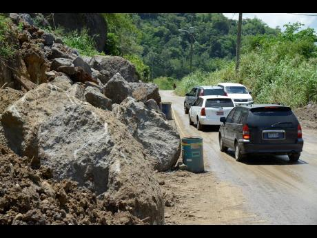 Motorists drive past boulders that were dug from the hillside in Broadgate, St Mary, amid works to widen the roadway.