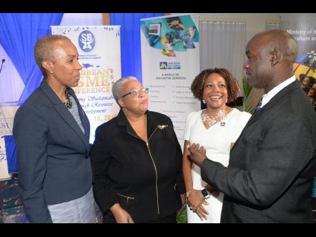 Hugh Johnson (right), president of the Small Business Association of Jamaica, has the attention of (from left) Fayval Williams, minister of science, energy and technology; Marlene Street Forrest, managing director, Jamaica Stock Exchange (JSE); and Dr Dana Morris Dixon, assistant general manager and chief marketing and business development officer at The Jamaica National Group.
