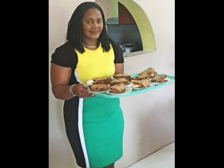 Andrea Mumby, regional operations manager,  Community and Workers of Jamaica Co-op Credit Union ready to serve bun and cheese to the children at Windsor Lodge Children's Home.