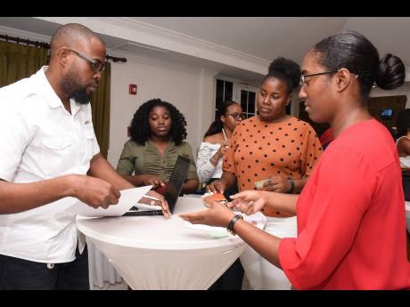 Participants gather to get their free credit reports done by representatives from JMMB, Portmore at the recent Boss Lady Ja event.