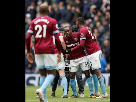 West Ham's Michail Antonio (centre) is celebrated by teammates at the end of the English Premier League match between Tottenham Hotspur and West Ham United at White Hart Lane in London, yesterday. West Ham won 1-0.