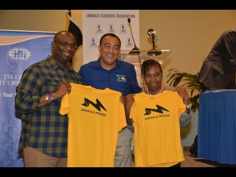 President of the Jamaica Teachers' Association (JTA), Dr Garth Anderson (left), and Assistant Secretary General, JTA, Dr Margaret Chin, show off the Jamaica Moves shirts presented to them by Health Minister Dr Christopher Tufton at the JTA's 18th Annual Education Conference on April 25 at the Hilton Rose Hall Resort and Spa, St James.