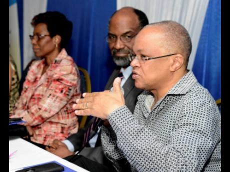 Dr Michael Abrahams (right), consultant obstetrician and gynaecologist emphasises a point during the question and answer section of the Dr Joseph St Elmo Hall Memorial Lecture Series on Cervical Cancer. Looking on are Dr Melody Ennis (left), acting director of the Ministry' of Health  Family Health Unit, and Earl Jarrett, board chairman, Jamaica Cancer Society.  The lecture was held at The Jamaica Pegasus hotel in Kingston yesterday.