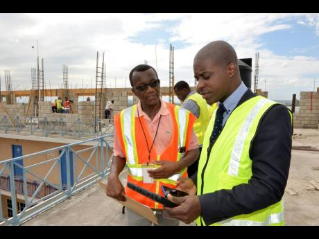 Director Principal of REDTRAC Major George Benson (left) and Ministry of National Security Project Manager Thaddeti Tulloch discuss expansion works being undertaken on the building at Twickenham, St Catherine, during a recent site visit.